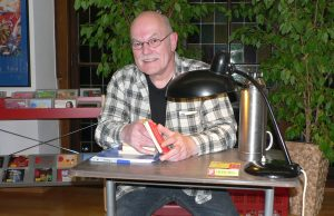 Thomas J. Lennartz, wie wir ihn kennen: schwarze Jeans, kariertes Hemd, alte Schreibtischlampe und Thermoskanne